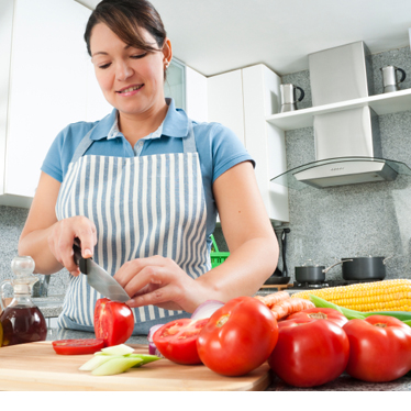 A woman chopping vegetables in a bright kitchen.
