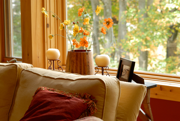 A couch near a window, with candles and flowers on a table in the background.