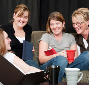 Four women gathered around a coffee table smiling.