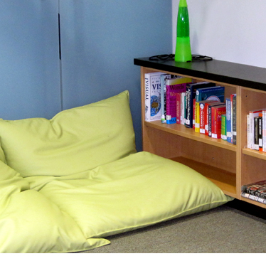 A reading nook with small bookshelf and pillows on the floor for sitting.