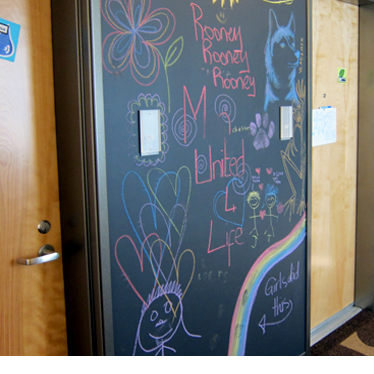 A chalkboard covered with kids' artwork