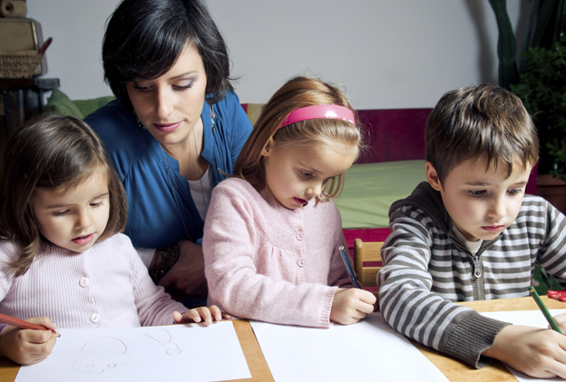 A woman doing an art project with her children