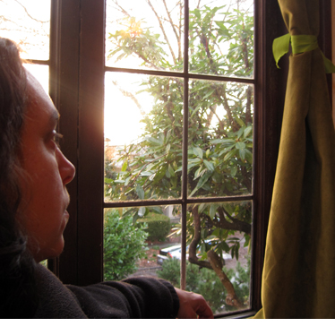 A woman looking out of a window as the sun sets.