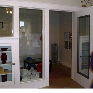 A playroom with big windows that allow kids inside to see out into the adjacent office space