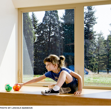 A child playing in a well-daylit room, in front of a large window.