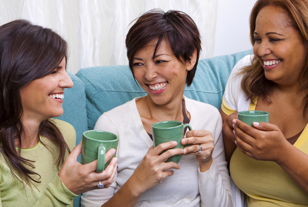 Three women drinking coffee together and laughing