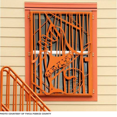 A window covered with a decorative metal grate that doubles as a secure cover