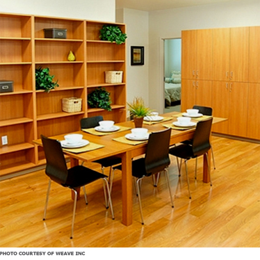 A dining room with wood floors and table, as well as simple hard chairs, all easy to clean.