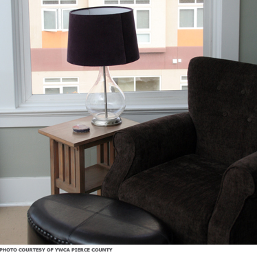 A chair next to a window. A lamp is on a side table nearby.