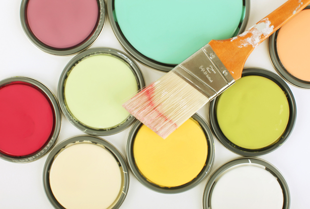 A paint brush sitting on several bright buckets of paint.